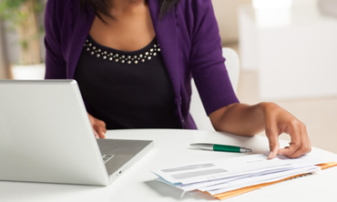 Woman balanceing checkbook while looking at computer